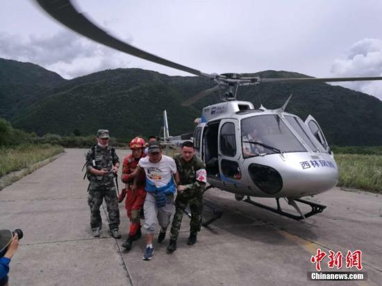 """8月10日,""""8.8""""九寨沟地震抗震救灾指挥部派出两架直升机编队飞行前往四川九寨沟景区搜救。图为被成功搜救出的被困民众。 中新网记者 安源 摄"""