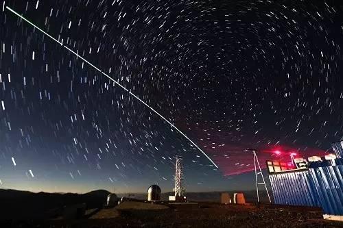 """资料图片:""""墨子号""""量子科学实验卫星与阿里量子隐形传态实验平台建立天地链路(2016年12月9日摄,合成照片)。"""