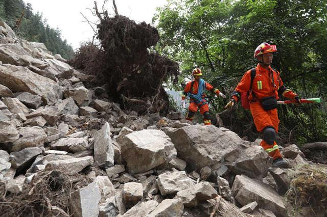 8月10日,两名搜救人员通过九寨沟景区镜海到五花海的滑坡路段。新华社记者 江宏景 摄