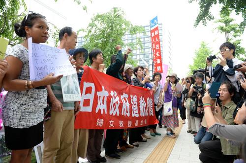 """资料图片:2014年6月2日,来自中国、日本、韩国、菲律宾等国家和地区的声援团体在日本东京举行示威,要求日本政府正视历史,对""""慰安妇""""进行道歉和赔偿。新华社记者 马平 摄"""