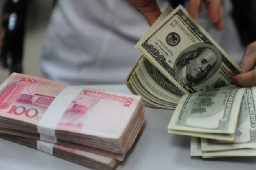 资料图片:中国农业银行海南琼海支行的营业员在清点美钞。新华社