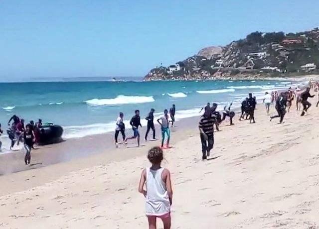 视频截图:8月9日,西班牙南部海滨,一名妇女注视着非洲非法移民冲上海滩。(新华/美联)
