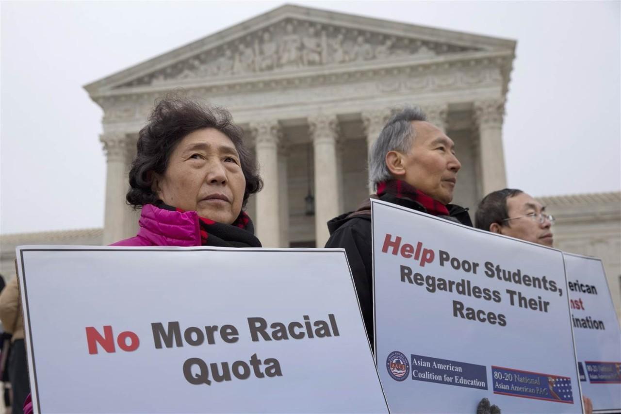 """图中抗议者手持的标语板上写着:""""废除宗族配额制""""""""帮助可怜的学生,不管他们来自哪个种族""""。"""
