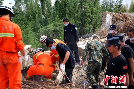 8月12日,在精河县托里镇地震灾区,公安民警和消防官兵正在坍塌的房屋中搜寻、转移灾民财产。 田向东 摄