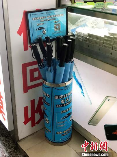 徐家汇地铁站一商户门口的共享雨伞借还点。 王子涛 摄