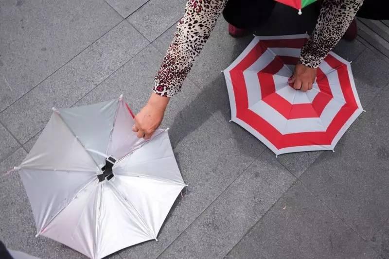每当有带孩子的游客询问价格,小贩们便会动作麻利地给孩子戴上伞帽。有些家长看到孩子可爱的模样,会掏钱买上一顶。