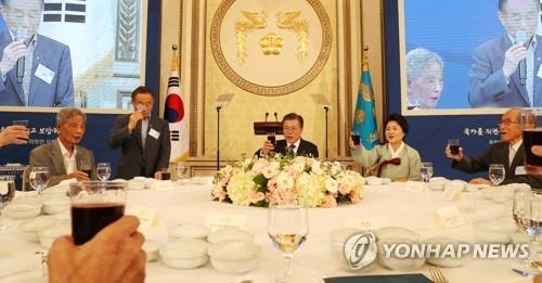 8月14日,在青瓦台,文在寅(右三)和夫人金正淑女士(右二)在午宴上举杯。(图片来源:韩联社)