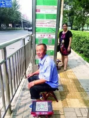 """▲有等车之人口运用""""共享马扎""""。北京晨报记者吴宁/摄"""
