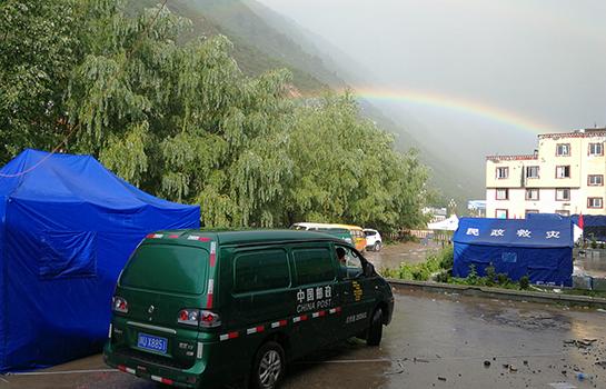 雨后彩虹下之邮车。