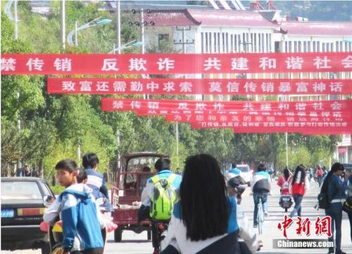 资料图:2015年10月13日,安徽安庆岳西街头拉起众多条幅开展禁止传销宣传。吴均奇 摄 图片来源:CFP视觉中国