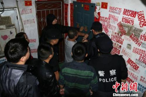 资料图:2016年11月19日,福建延平,民警用撬棍撬开传销窝点防盗门。 丁晨 摄