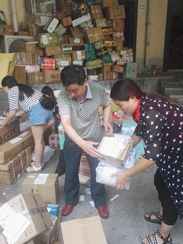 8月11日,漳扎邮政支局员工联络用户投递包裹。