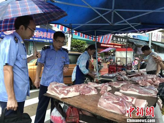 执罪人员在肉摊进行检查。 钟欣 摄