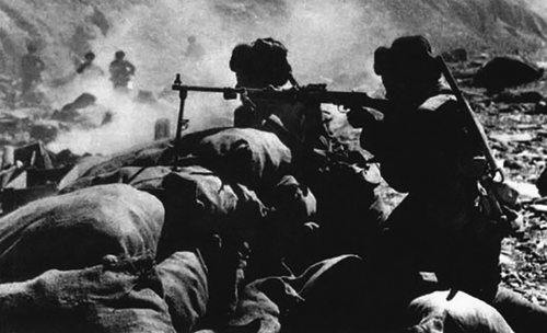 1962年中印疆域自卫还击战时代,解放军用机枪向敌人开火。