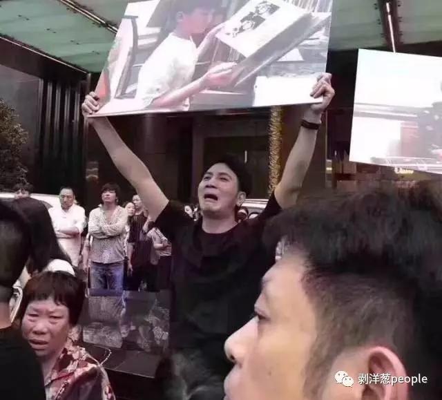 林生斌举牌表达损失妻儿的悲痛。