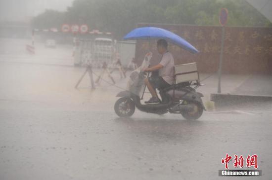 7月31日,暴雨侵袭福州,市平易近艰巨出行。中新社记者 王东明 摄