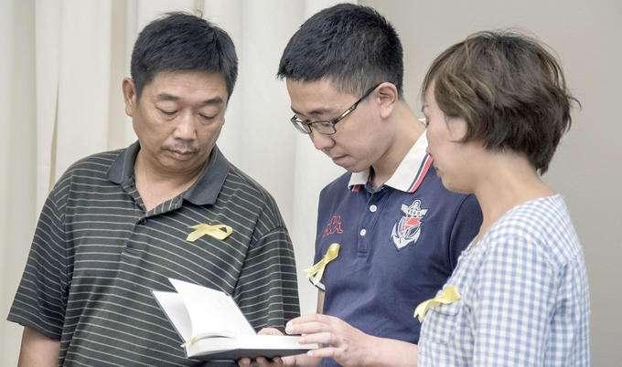 章莹颖的家人在发布会上看她的日记