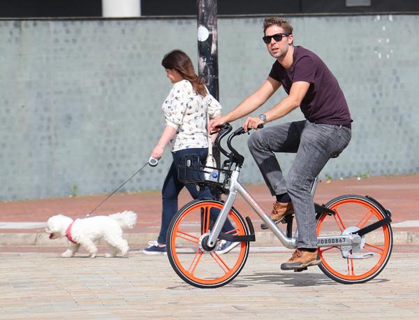 英国曼彻斯特一名男子在骑共享单车。