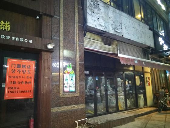 """8月22日,上海虹泉路韩人商街的某餐厅门口贴出了""""转让""""的通告,旁边的市肆也已摘下招牌,处于休业状态。(图片泉源:韩国《中央日报》)"""