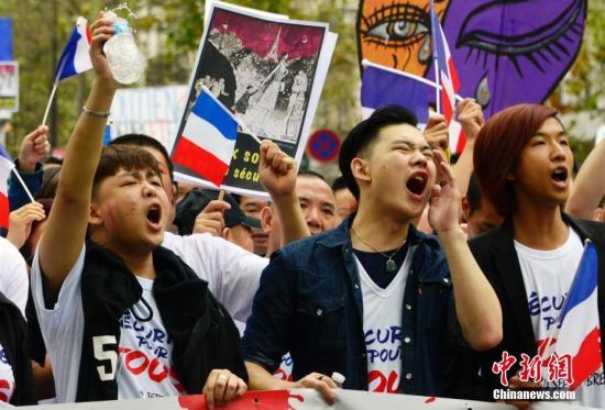 资料图:法国华社在巴黎市中央举行阵容浩荡的聚会会议游行,悼念遇暴力抢劫被殴致死的旅法侨胞张朝林。图为到场游行的华人奋力发声。 中新社记者 龙剑武 摄