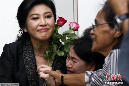 资料图:当地时间2017年8月1日,泰国前总理英拉抵达最高法院出席大米收购案结案辩护陈词,民众送上玫瑰花