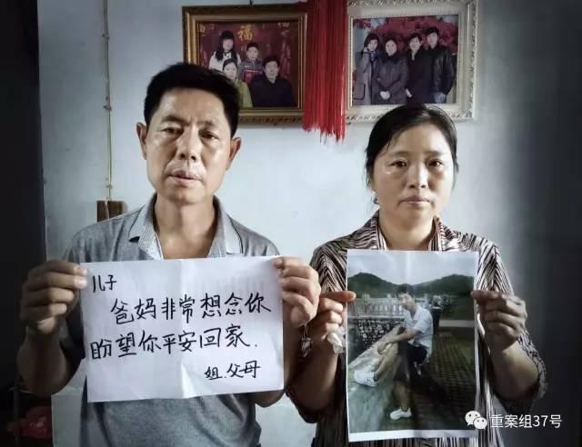 ▲8月20日,河南信阳,邓杰的家中。邓杰的父母拿着儿子的照片以及盼望儿子平安回家的话。背后墙上是其全家福。新京报记者尹亚飞摄