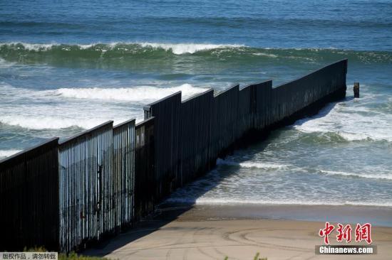 资料图:美墨边境的高墙,一直延伸到海里。