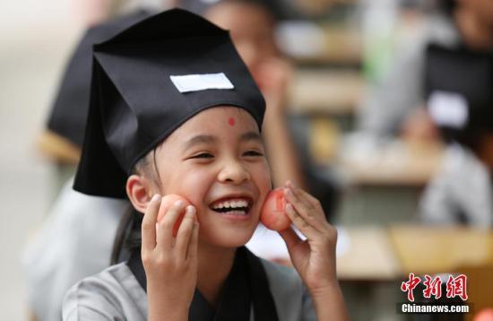 """材料图:小学举办一年级重生退学""""开笔礼""""典礼上,一逻辑学生展现教师发的""""红鸡蛋""""。 谭凯兴 摄"""