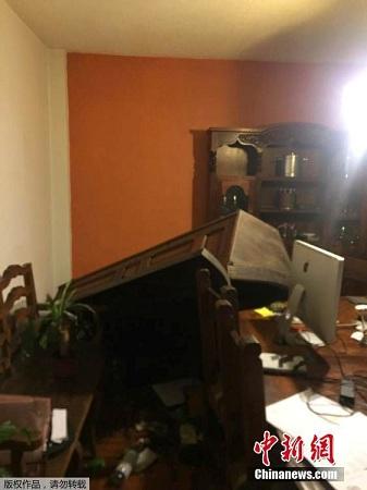 图为墨西哥一所公寓内,原本靠墙的柜子倒在地上,屋内一片狼藉。