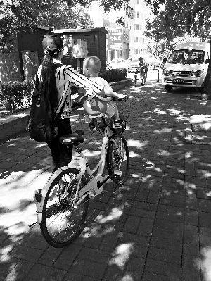↑北京街头,一名家长在共享单车上装了儿童座椅。
