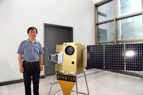 """资料图片:中国科大内,潘建伟与""""墨子号""""量子卫星模型合影。新华社发"""
