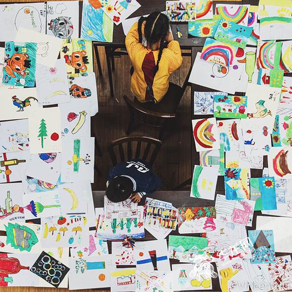 两个正在绘画的孤独症儿童。寻影季摄影工作室供图 华龙网发