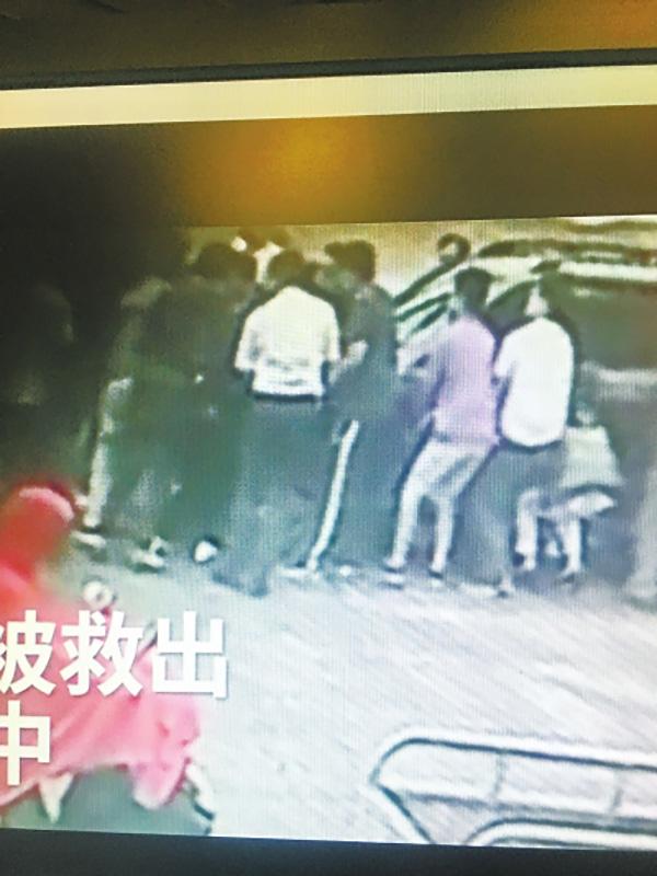 记者翻拍大伙合力抬车救人的视频画面。