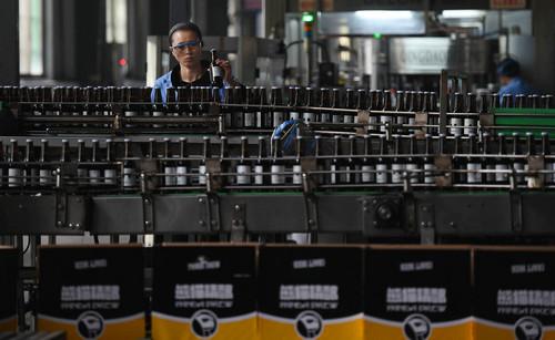 """材料图片:2016年4月15日,一位工作人员在位于湖南益阳的""""熊猫精酿""""装瓶车间里工作。新华社记者 李尕 摄"""