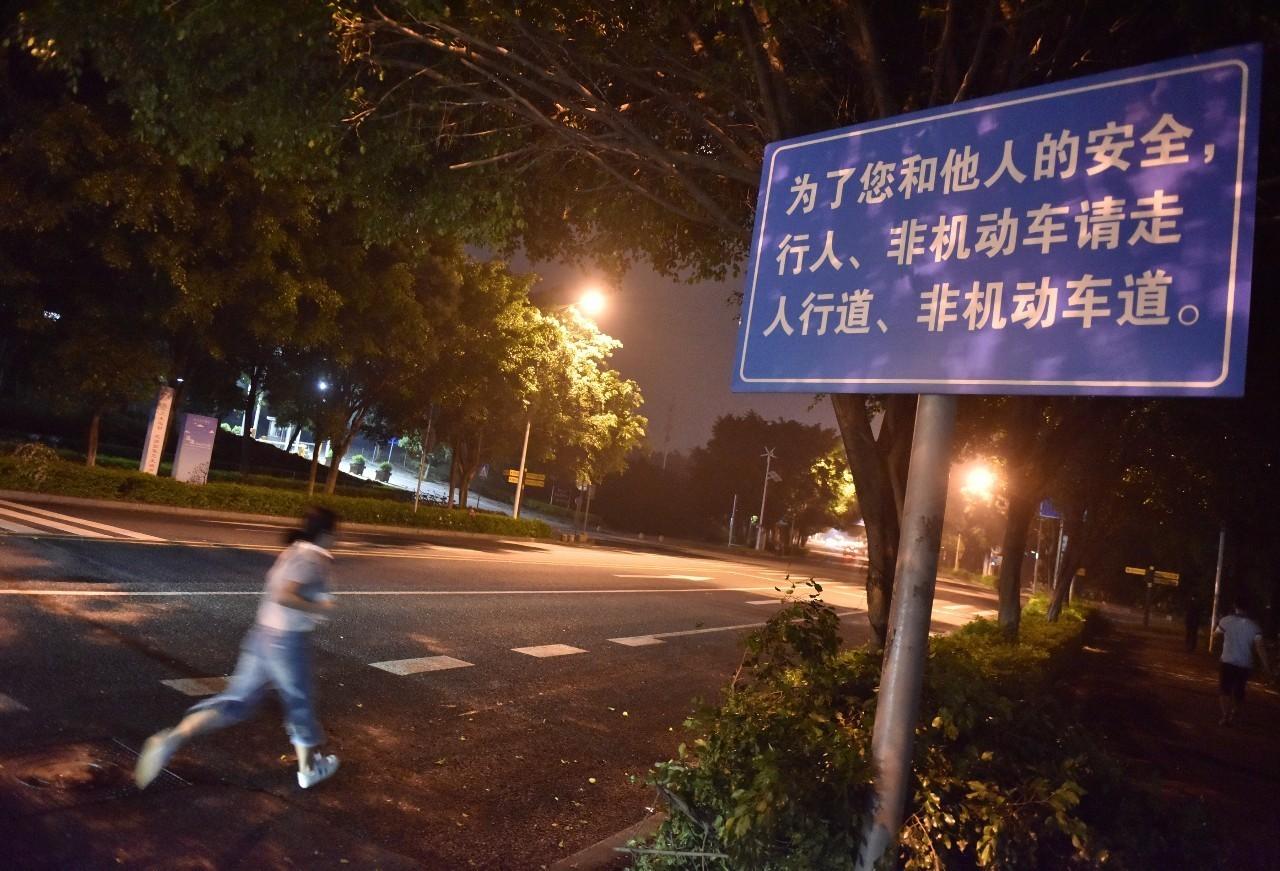 大学城内环部分路段竖有交通安全警示牌,然而还是有市民在机动车道飞奔。 信息时报记者 朱元斌 摄