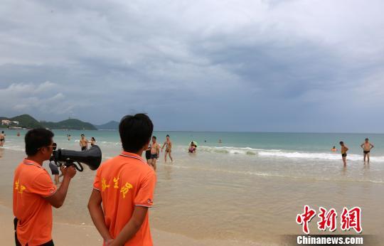 9月14日,三亚大东海景区海滩关闭,景区救生员提醒旅客连忙离开海滩。 尹海明 摄
