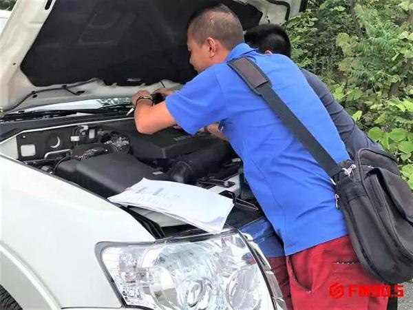 郴州市公安局交警支队万华汽车城车辆管理分所工作人员(蓝衣男子)在检查李先生的帕杰罗。