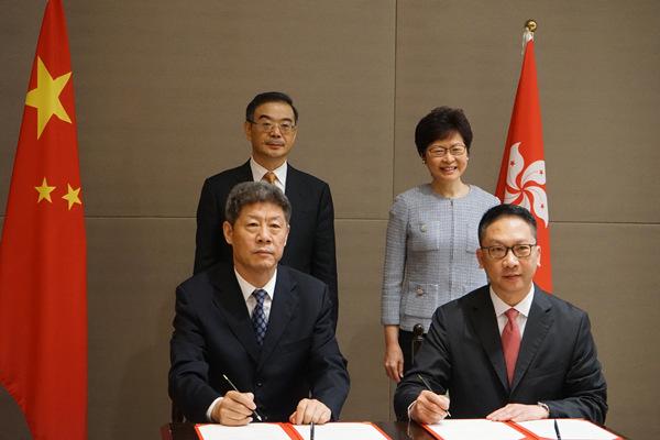 图为李少平、袁国强独特签订《对于增强最高国民法院与喷鼻港特殊行政区当局律政司交换与配合纪要》。