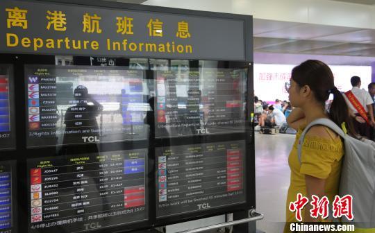 9月14日下午,旅客在三亚凤凰国际机场查看离港航班信息,屏幕上显示不少航班已经取消。 尹海明 摄