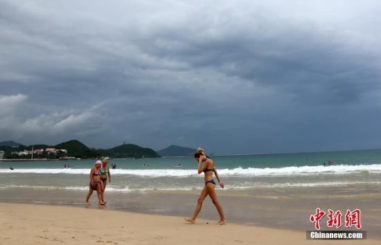 """9月14日,海南三亚大东海景区,海面上乌云密布,有游客不顾台风警报在海滩上逗留。受今年第19号台风""""杜苏芮""""的影响,三亚海滩关闭,暂停涉海旅游。 中新社记者 尹海明 摄"""
