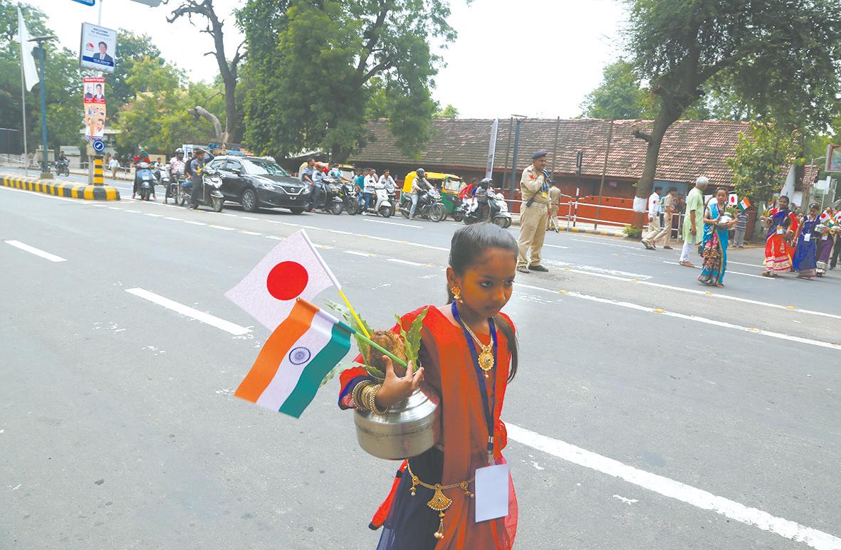 """13日,一名印度少女手拿印日国旗参加在艾哈迈达巴德举行的欢迎日本首相安倍的""""路演""""。"""