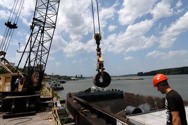 """▲中国的""""一带一起""""倡议为巴尔干半岛带来机缘。图为塞尔维亚斯梅代雷沃,工人把一卷钢材装上驳船。一家中国企业买下了该市的钢铁厂。(美联社)"""
