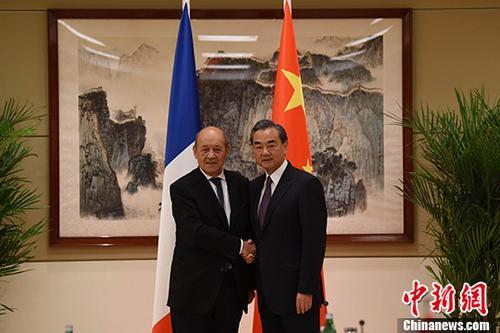 外地工夫9月19日,中外洋交部长王毅(右)在纽约列席第72届联大时代会晤法外洋交部长勒德里昂。 中新社记者 刁陆地 摄