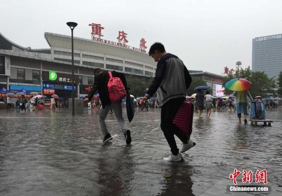 资料图:重庆降雨致地面积水,市民冒雨淌水前行。 周毅 摄