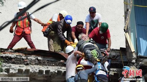 搜救人员将一位老人从废墟中救出。