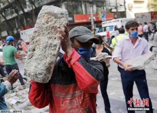 墨西哥城的一处倒塌的建筑废墟旁,志愿者徒手搬走石块,以方便救援行动展开。