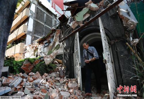 墨西哥城Condesa区,一名男士从楼房里出来,门外是满地的房屋瓦砾,建筑已成废墟。