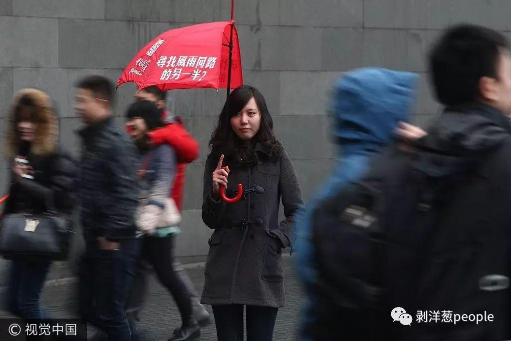 """2012年情人节,一家婚恋网站的模特撑开半把雨伞,上面写有""""寻找风雨同路的另一半""""的字样,站立在人流不息的上海南京西路街头。图片来自视觉中国"""