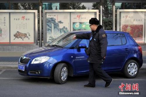 图为停车治理员为车主指挥倒车入位(资料图)。中新网记者 金硕 摄