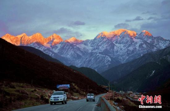 图为康定城外雪山之下的川藏318公路。 中新社发 刘忠俊 摄